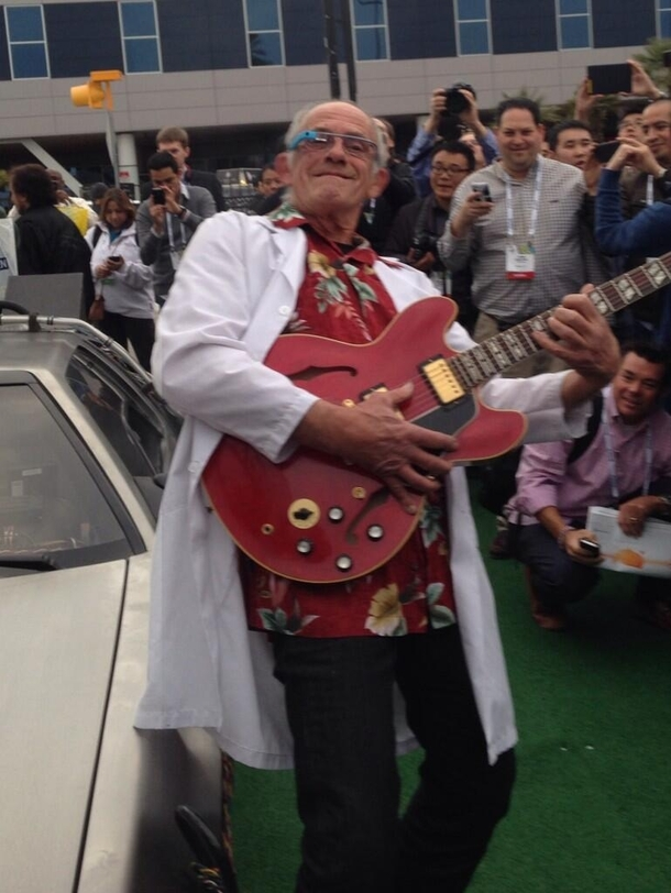 Christopher Lloyd next to a DeLorean wearing Google Glass and playing Marty McFlys Gibson from CES yesterday