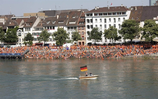 Dutch fans are watching a game against Germany on a big screen over the river Suddenly