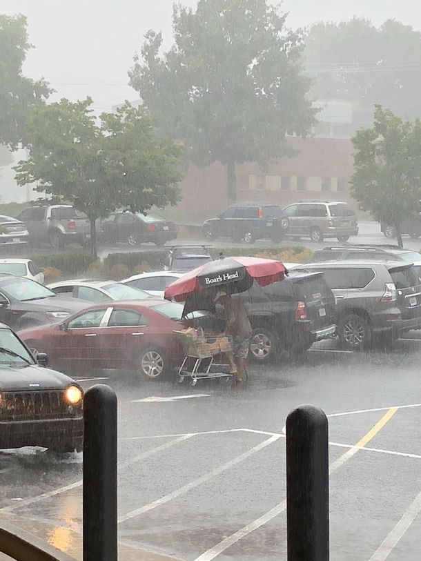 Guy takes the grocery store picnic table umbrella to load his groceries