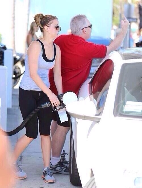 Jennifer Lawrence filling her tank while her dad flicks off paparazzi