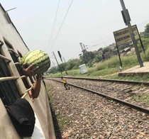 A guy bought this watermelon from a vendor while the train made a quick stop He had to hold it like this because it didnt fit between the bars and the train resumes its journey
