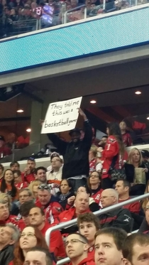 Black dudes sign at a hockey game