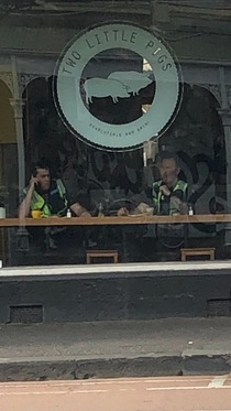 Cafe across from me is called  little pigs There just happened to be  police officers sitting under the sign