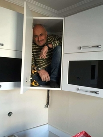 Contractor gets in the cabinet he just built to prove its sturdiness