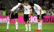 Germanys central defenders  and  bending down to talk to their captain