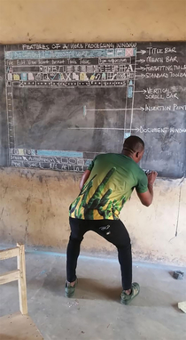 Having no computer this teacher from Ghana teaches Word on a backboard