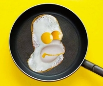 Homer Simpson using the medium of fried eggs