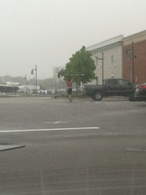 Just some dude lifting weights in the rain in a mall parking lot