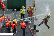 Kids playing with a water hose during coast guard demonstration