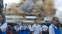 Malaysians students smiled as they evacuate from their burning school building