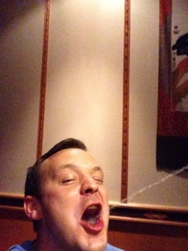 My brother took a selfie while getting sake shot in his mouth at a hibachi restaurant