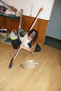 My girlfriend insists on showing me how to sweep up properly despite her broken arm