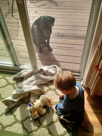 My son feeding his fake dog goldfish while his real dog sits outside pissed