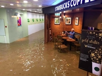 old man continues reading news while starbucks gets flooded