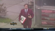 Ron Burgundy carrying a box of donuts and a  of Old English Lost in Millford looking for the ESPN studio