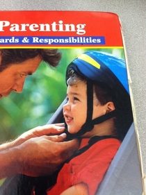 The dad on my Child Development book is putting the kids helmet on backwards