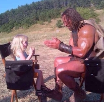 The Rock on set and in costume as Hercules playing party cake with a  year old