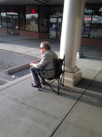 They removed the bench from in front of the Liquor store so this guy brings his own seat