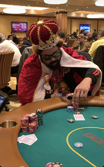 This guy dressed as the Burger King at a poker table with Oreos in his chip holder