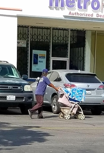 This nice dad is using a stroller to push his newborn baby beers