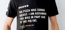 This Pizzeria employee is wearing T-Shirts with quotes from nasty yelp review