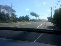 Tried to take a photo of a grasshopper on my windshield but it looks like its giant and destroying the town posted in rmildlyinteresting