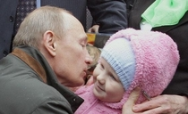 Vladimir Putin kissing a baby Just prior to this the baby attacked a journalist bit his leg and drew blood